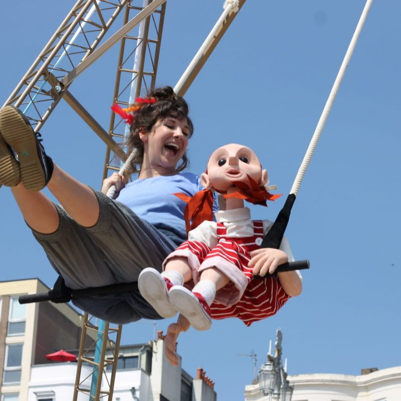 Puppet and performer on a swing