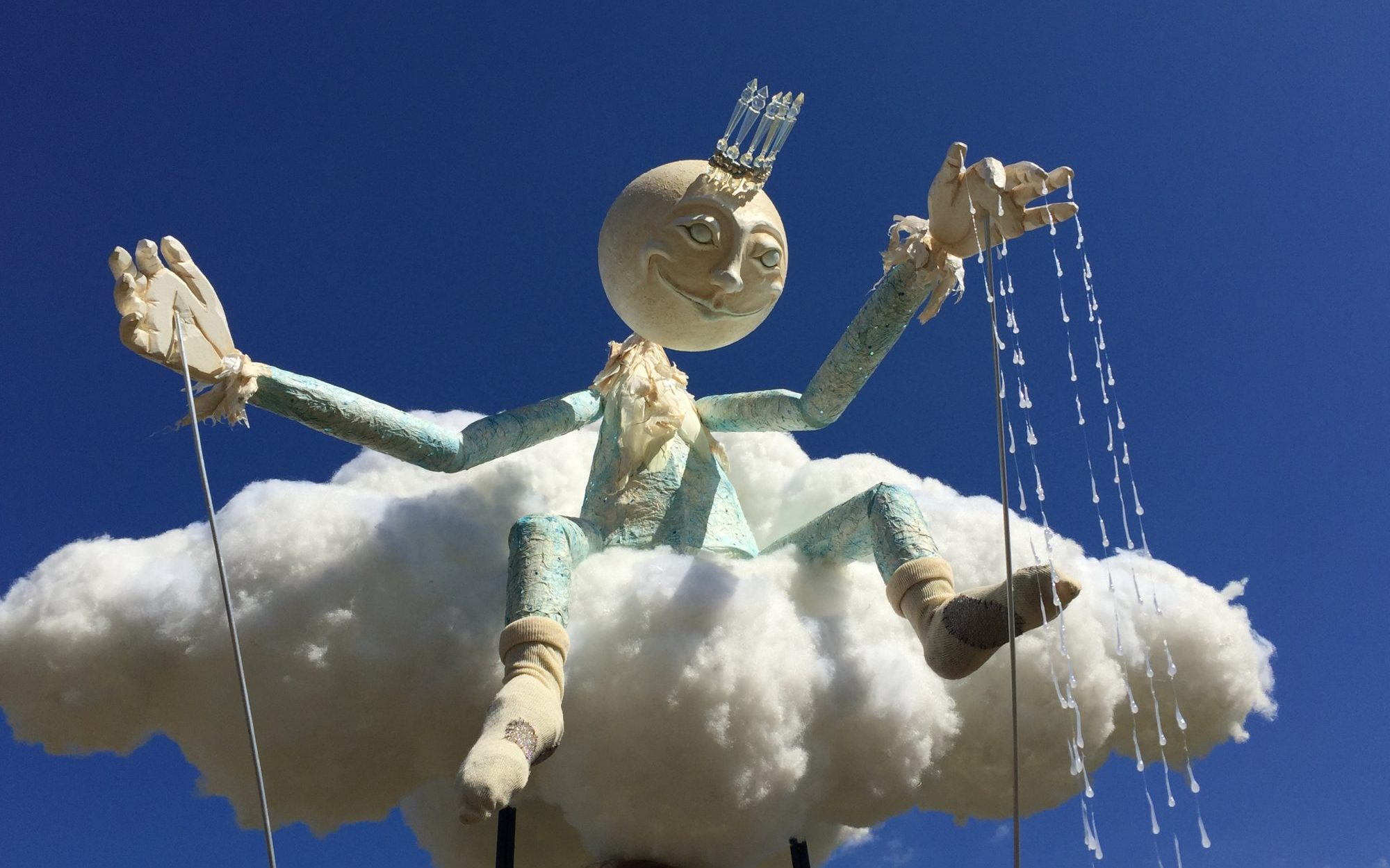 Moon faced walkabout puppet sat on a cloud