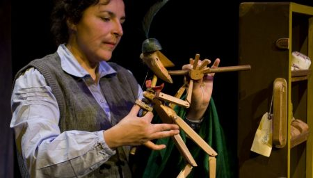 Female theatre performer operating wooden Pied Piper puppet